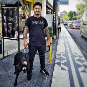 Kuta Tattoo Studio owner Tama with black pit bull dog