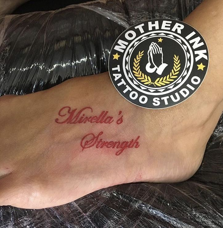 Red cursive lettering tattoo by Mother Ink
