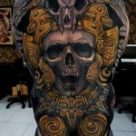 Skull backpiece black and gold tattoo by Ata Ink in Bali